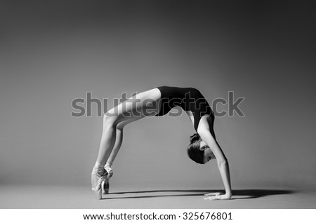 Ballerina in black outfit posing in bridge position. Studio background, grayscale image. - stock photo