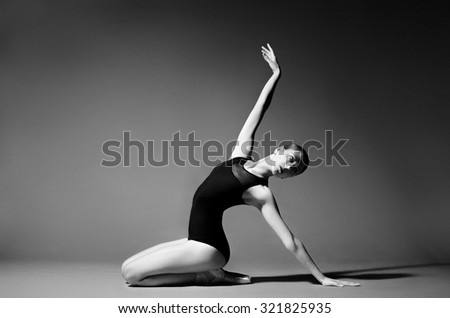 Ballerina in black outfit posing on studio background. Extreme flexibility, grayscale image. - stock photo