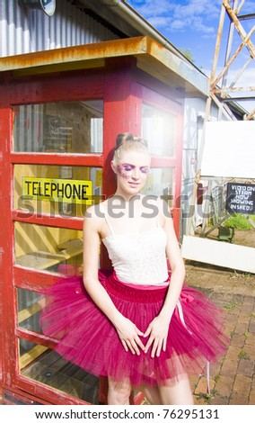 Ballerina In Pink Tutu Waits With Eyes Closed Next To A Phone Box In The Sun For A Phone Call In A Communication Conceptual - stock photo