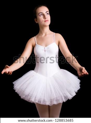 Ballerina posing against black background - stock photo