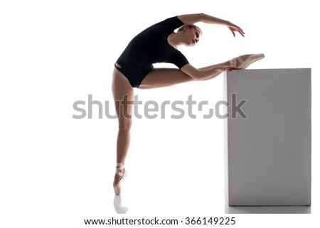 Ballerina putting her leg on cube while warming up - stock photo