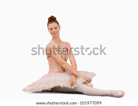 Ballerina sitting against a white background