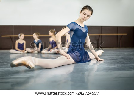 ballerina sitting on the floor in the splits and  dance class dancers practicing on the background - stock photo