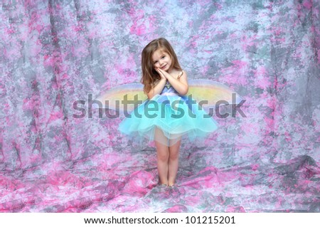 Ballerina wearing  aqua tutu and fairy wings stands in a room filled with pink and grey.  Her hands are folded against her cheek. - stock photo