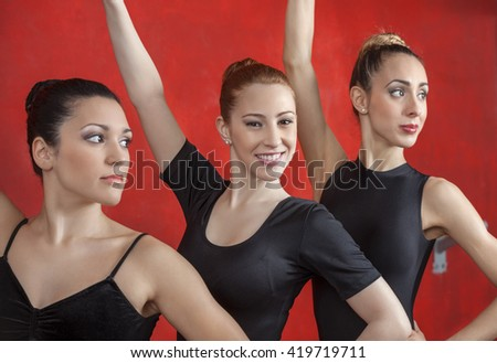 Ballerina With Friends Performing Against Red Wall - stock photo