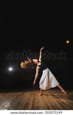 Ballerina, young brunette dancer girl in a white skirt, dance poses on stage in theater with spotlight. barefoot dancer. - stock photo