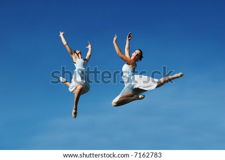 Ballerinas jumping against a blue sky - stock photo