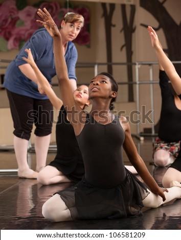 Ballet class teacher helps students practice dance moves - stock photo