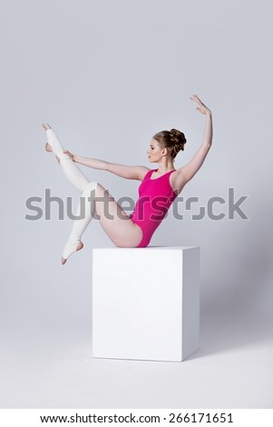 ballet dancer. attractive young woman gymnast on a white cube - stock photo
