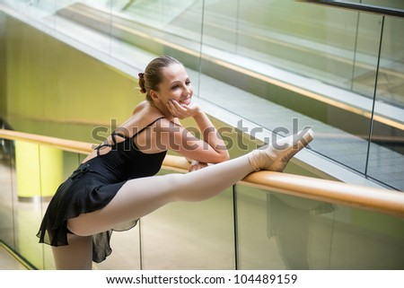 Ballet dancer (ballerina) dancing in modern shopping premises at escalator - stock photo