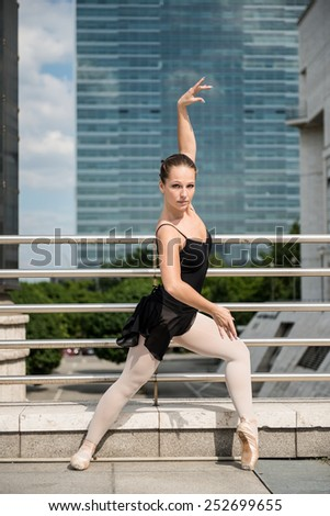 Ballet dancer (ballerina) dancing on street with business buildings in background - stock photo