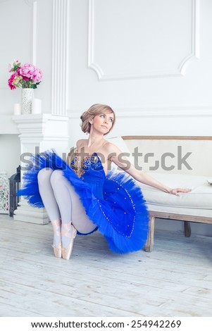 ballet dancer in blue tutu trainers in a light luxury interior