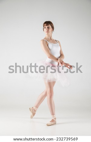 Ballet dancer in white tutu posing on white background - stock photo