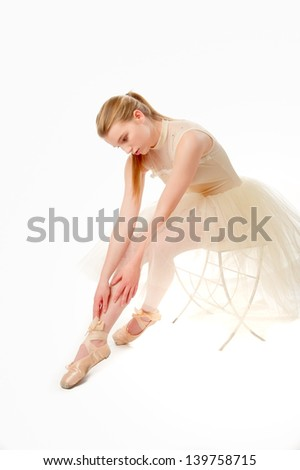 ballet dancer sitting in a tutu stretching on a white background - stock photo