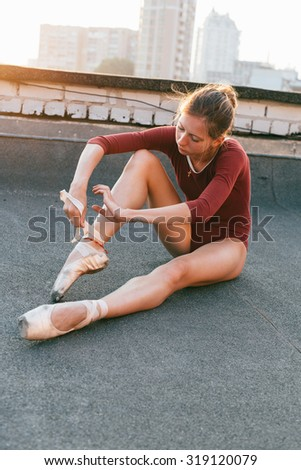 Ballet dancer sitting on the roof and putting on her pointe shoes in the morning