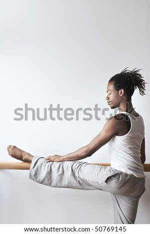Ballet Dancer stretching at bar - stock photo