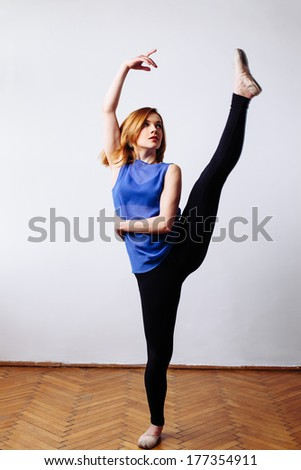Ballet dancer stretching her leg - stock photo