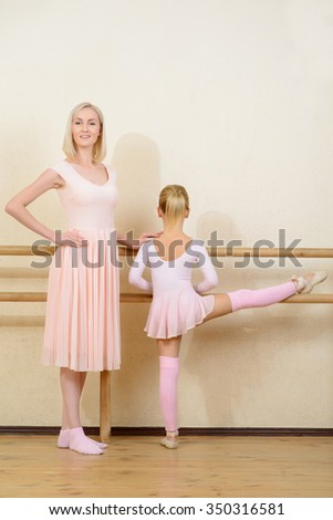 Ballet lesson. Young woman teaching her little apprentice to do basic stretching.