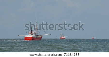 Ballet of trawlers - Fishing boats pull the trawls near the Danish island of Romo. - stock photo
