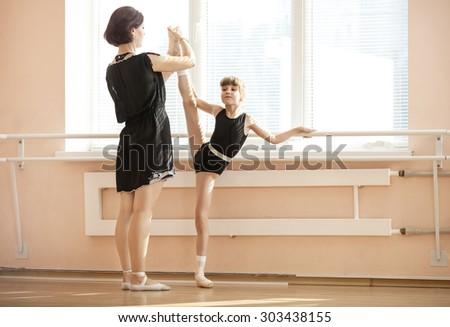 Ballet teacher adjusting leg position of young ballerinas at barre - stock photo