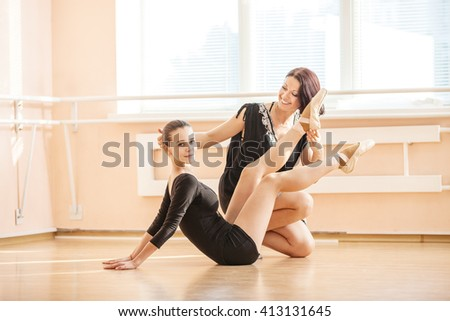 Ballet teacher showing young girl how to perform exercise on floor and smiling - stock photo