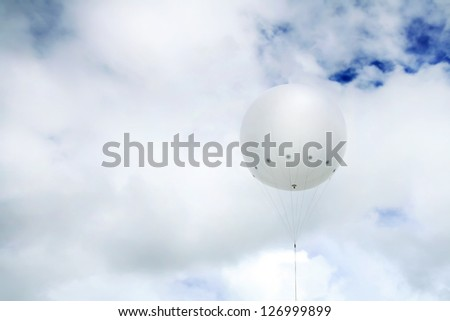 balloon big white in the sky blue with lots of white clouds high in the atmosphere