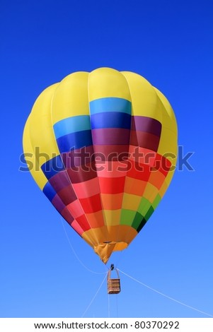 balloon colorful with vivid colors flying in blue sky - stock photo