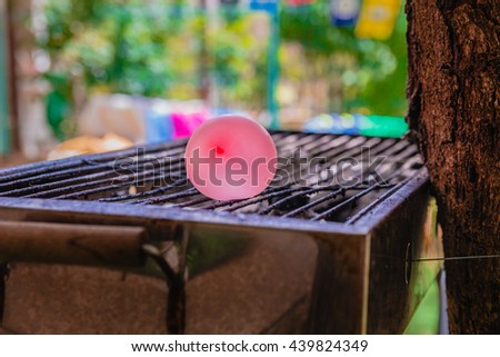 Balloon filled with water placed on a hot grill. An experiment that tests what would be the reaction of the balloon with the cold water to the heat comes off the grill. - stock photo