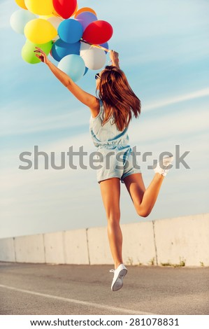 Balloon fun. Rear view of happy young woman holding colorful balloons and jumping outdoors - stock photo