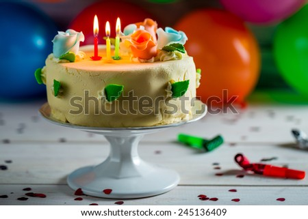 Balloons and birthday cake with candles for a party - stock photo