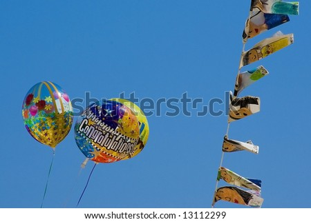 Balloons and flags in blue sky - stock photo