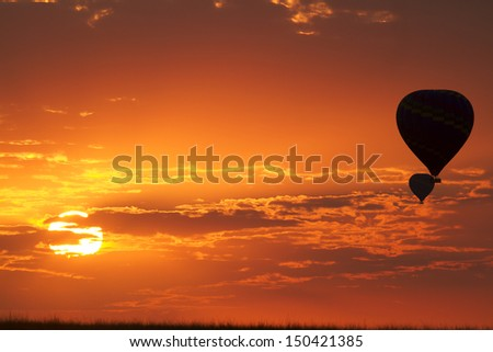 Balloons flying in early morning red sky - stock photo