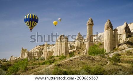 Balloons flying over Love Valley near Goreme in Cappadocia Turkey - stock photo