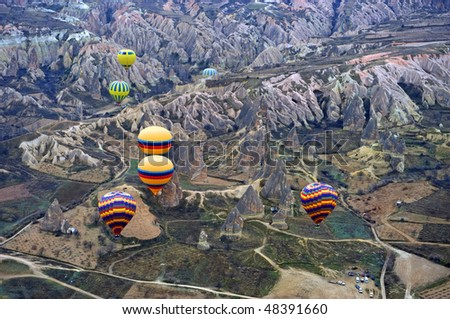 Balloons flying over the landscape of Cappadocia - stock photo