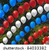 Balloons of red, blue and white against the dark foliage. - stock photo