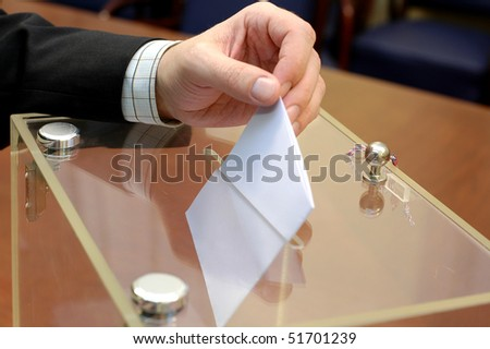 ballot box and hand putting a blank ballot inside, elections and democracy concept - stock photo