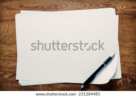 Ballpoint pen lying on sheets of blank white paper with copyspace for your handwriting or text, overhead view on a wooden desk - stock photo