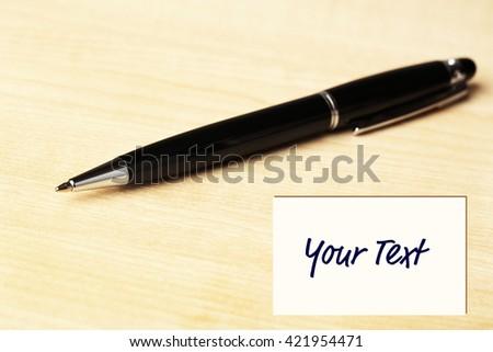 Ballpoint pen on wooden table background - stock photo