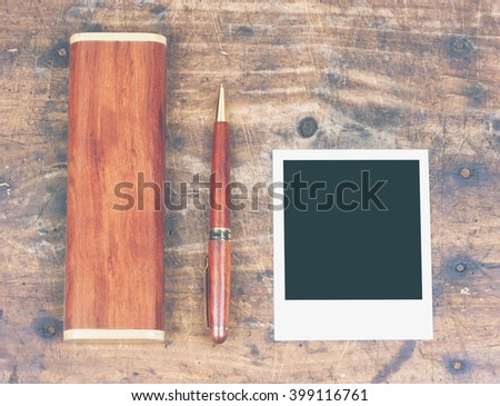 Ballpoint with box and photo frame on wooden table with vintage filter effect - stock photo