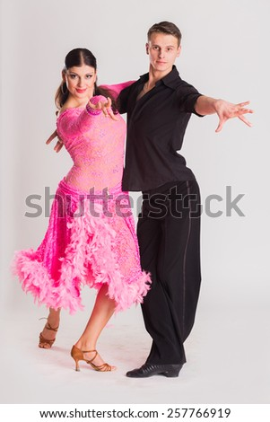 Ballroom dancers dancing. Dancers on a light background. Man and woman dancing. Man and woman posing in dance position. - stock photo