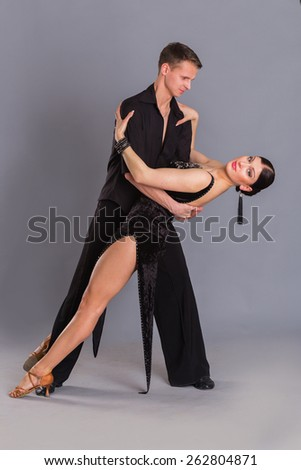Ballroom dancing. Man and woman posing in dance pose on light. Man and woman dancing ballroom dances. Beautiful man and woman doing the dance steps. Dance poses. - stock photo