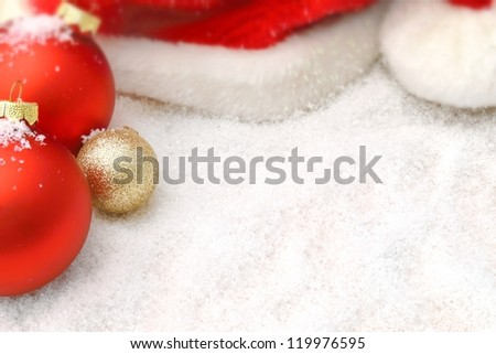 Balls and Santa hat in the snow - stock photo