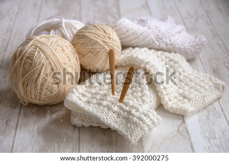 balls of white yarn and knitting needles