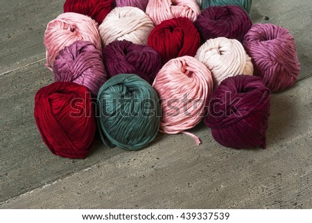 balls of wool on rusty wood table background - stock photo