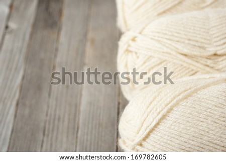 balls of wool on weathered wooden table