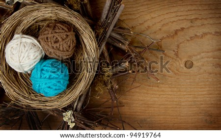 Balls of yarn in a nest easter decoration, on a wooden background, room for copy space. - stock photo