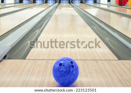 Balls on bowling alley against ten pins - stock photo