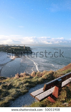 ballybunion bench in winter snow storm with view of castle beach and cliffs - stock photo
