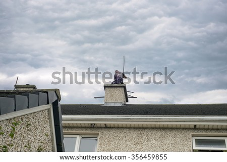 Ballybunion, County Kerry, Ireland - September 1, 2014:chimney sweep busy cleaning chimney on top of a house - stock photo