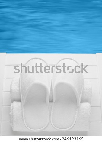 Balneo, spa, hotel, home, wellness slippers with rolled towels on pier with water background - summer, sauna time - space for text - stock photo